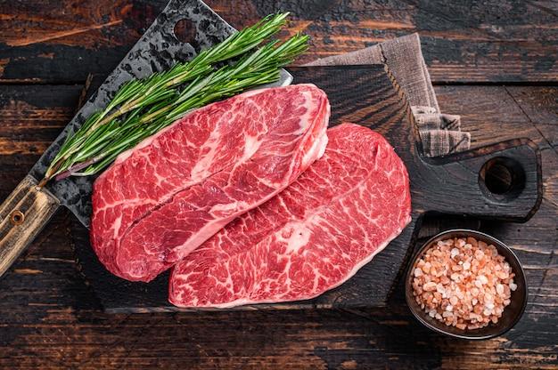 Nieugotowane surowe łopatki z łopatki lub płaskie steki z mięsa wołowego na drewnianej desce rzeźniczej z tasakiem do mięsa. ciemne drewniane tło. widok z góry.