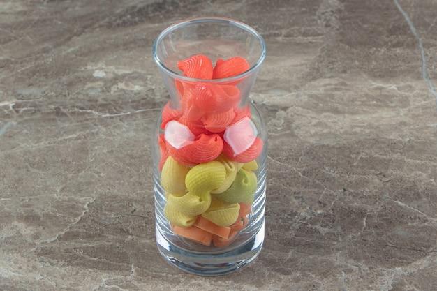 Nieugotowany kolorowy makaron w szklanym kubku.