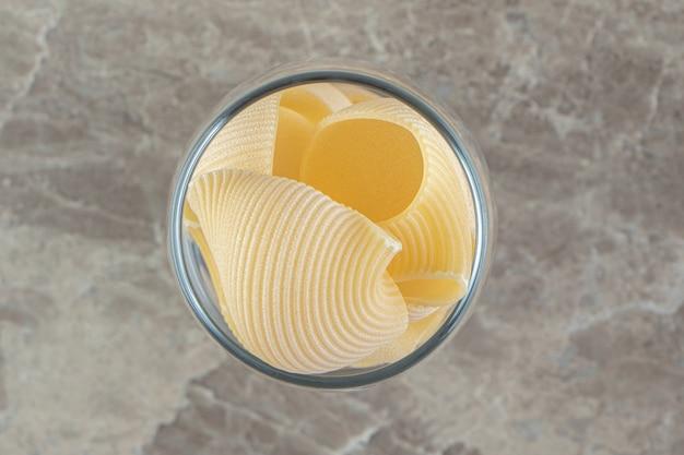 Nieugotowany makaron conchiglie w długim szkle.