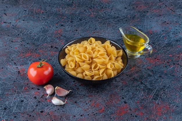 Nieugotowany makaron łuskany w szklanej misce ze świeżymi czerwonymi pomidorami i czosnkiem.