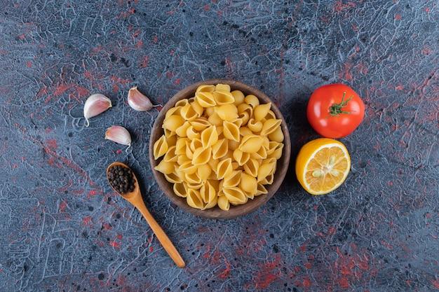Nieugotowany makaron z łupinami w drewnianej misce ze świeżym czerwonym pomidorem i pokrojoną w plasterki cytryną.