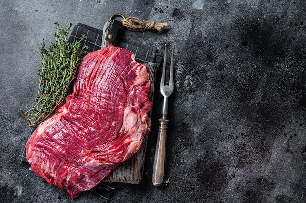 Nieugotowany surowy stek wołowy lub wołowy na desce mięsnej. czarne tło. widok z góry. skopiuj miejsce.