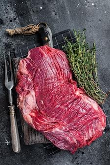 Nieugotowany surowy stek wołowy lub wołowy na desce mięsnej. czarne tło. widok z góry.