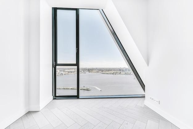 Nieumeblowane wnętrze pokoju z parkietem i białymi ścianami i oknem ściennym w luksusowym mieszkaniu