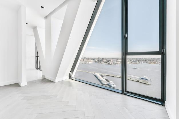 Nieumeblowany pusty pokój z parkietem i panoramicznym oknem ściennym z widokiem na rzekę miasta w słońcu