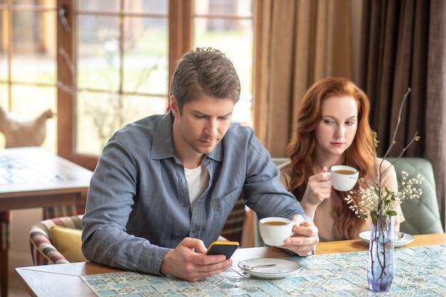 Nieuwaga. zainteresowany mężczyzna patrzący na smartfona i ciekawska kobieta siedząca pijąca kawę w restauracji po południu