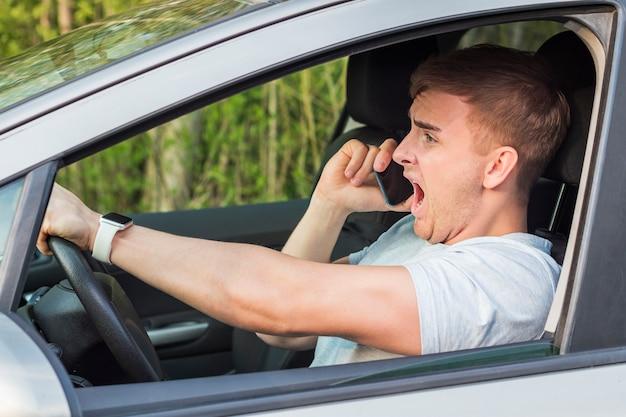 Nieuważny człowiek, przestraszony, przerażony facet, kierowca, zszokowany mężczyzna, który ma mieć wypadek drogowy, prowadzący samochód, krzycząc krzycząc, trzymając w ręku, rozmawiając przez telefon komórkowy na drodze. niebezpieczna sytuacja