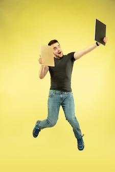 Nieważki. pełnej długości portret szczęśliwy człowiek skaczący z gadżetami na białym tle na żółtym tle