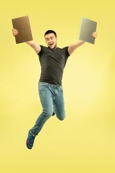Nieważki. pełnej długości portret szczęśliwy człowiek skaczący z gadżetami na żółtym tle.