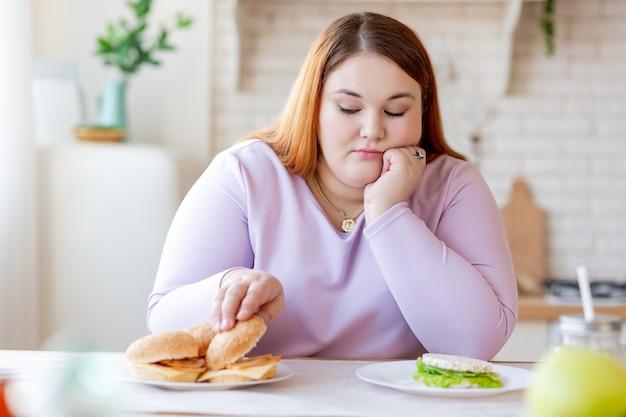 Niewesoła, pulchna kobieta patrząca na burgera, myśląc, żeby go zjeść, czy nie