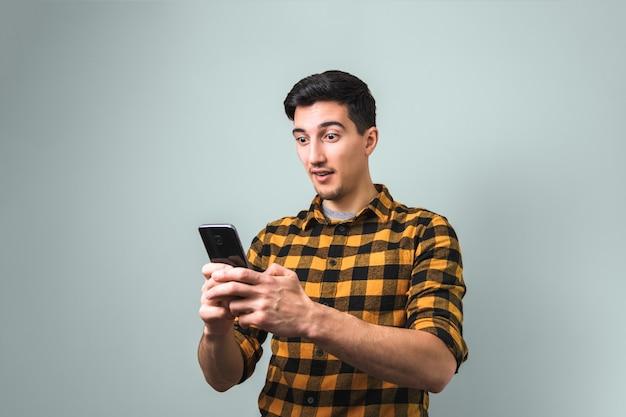 Niewiarygodne szczęśliwe wieści. zaskoczony mężczyzna w żółtej koszuli trzyma telefon