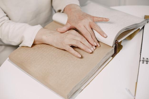 Niewidoma dojrzała kobieta czyta książkę braille'a w domu