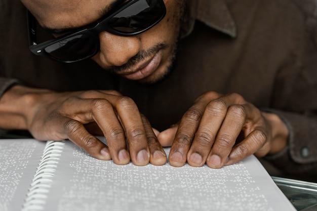 Niewidomy czyta alfabetem braille'a