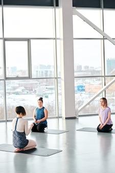 Niewielka grupa młodych kobiet siedząca na matach przed instruktorką jogi i fitness, wyjaśniająca im zasady treningu na siłowni