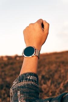 Niewielka ostrość nakręciła zegarek na ręce kobiety w dżinsowym płaszczu