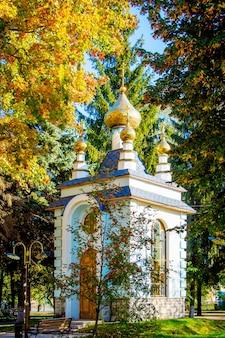 Niewielki budynek cerkwi otoczony jesiennymi drzewami