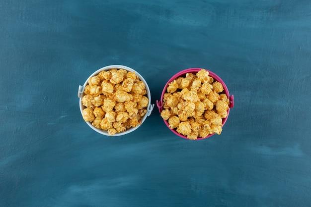 Niewielkie wiaderka wypełniały brzegi karmelowym popcornem na niebieskim tle. zdjęcie wysokiej jakości