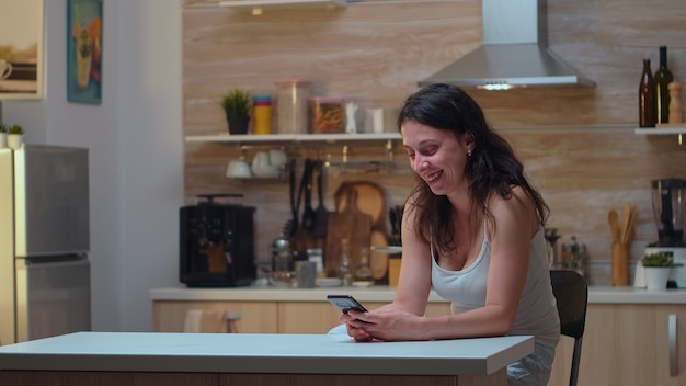 Niewierna żona rozmawiająca z mężem w domu. zazdrość zdesperowany mężczyzna oszukany, zły, sfrustrowany i zirytowany, znajduje wiadomości o niewierności na telefonie kobiety siedzącej w kuchni.