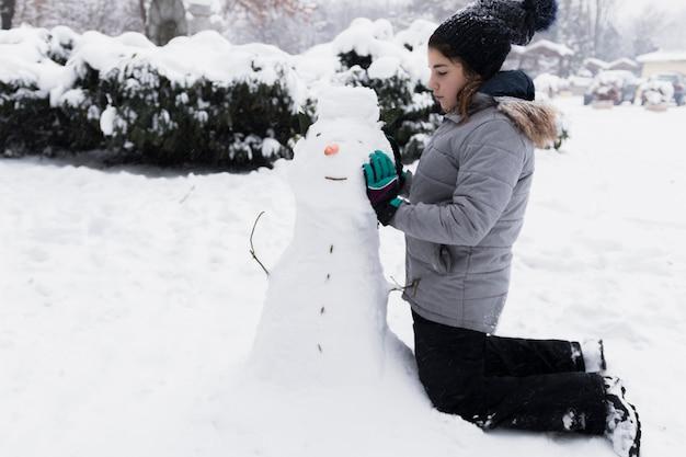 Niewinna dziewczyna dotyka bałwana w zimie
