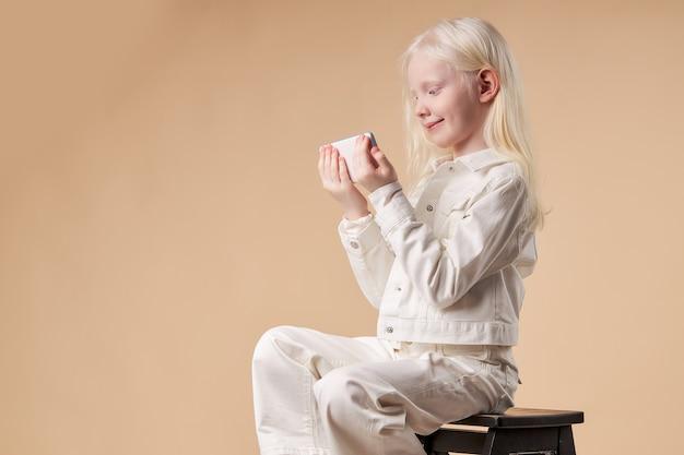 Niewinna niezwykła dziewczynka albinos oglądająca filmy na smartfonie