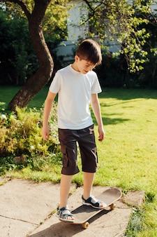 Niewinny chłopiec bawić się deskorolka w parku