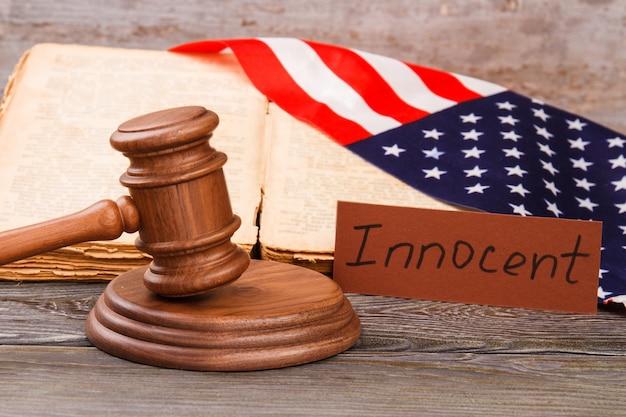 Niewinny wyrok w sądzie usa. drewniany młotek i flaga usa.