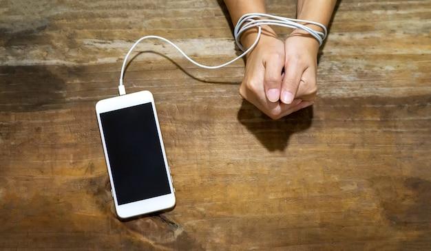 Niewolnik koncepcji mediów społecznościowych, ręka zablokowana kablem i telefonem komórkowym