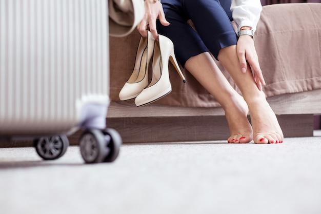 Niewygodne buty. miła młoda kobieta dotykająca stóp zmęczona po chodzeniu na wysokich obcasach