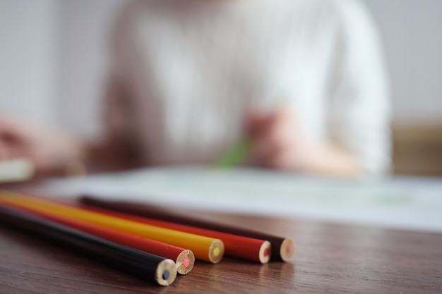 Niewyraźna dziewczyna rysuje ołówkami, selektywna ostrość