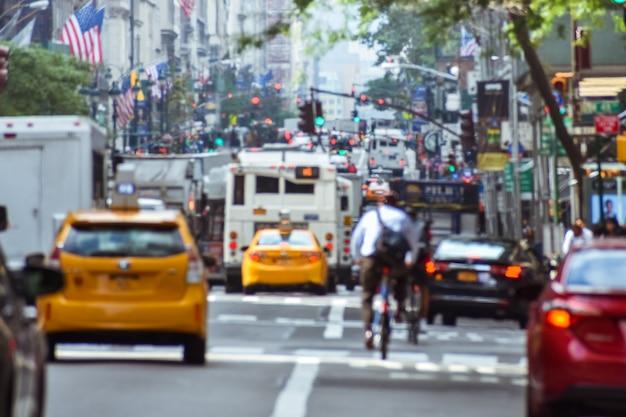 Niewyraźna koncepcja szalonej aktywności życia w nowym jorku. samochody, transport publiczny, rowerzyści, piesi, znaki i flagi. koncepcja zatłoczonego miasta i ruchu ulicznego. manhattan, nowy jork. nas
