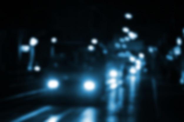 Niewyraźna nocna scena ruchu na jezdni. nieostry obraz samochodów podróżujących ze światłami reflektorów.