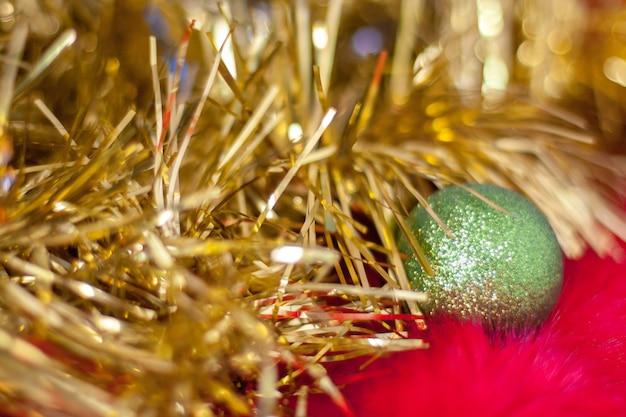 Niewyraźne abstrakcyjne tło bożego narodzenia złotej blichtru i zielonej świątecznej kuli