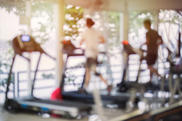 Niewyraźne centrum fitness z urządzeniami do ćwiczeń wysiłkowych i treningiem siłowym. liczby ludzi biegających na bieżniach w siłowni.