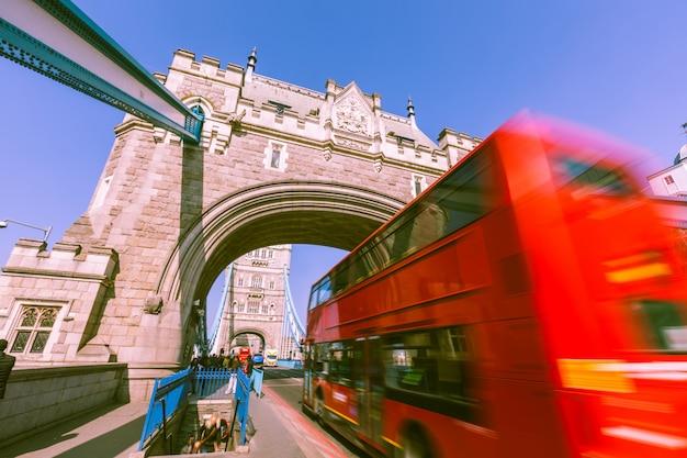 Niewyraźne czerwony autobus na tower bridge w londynie