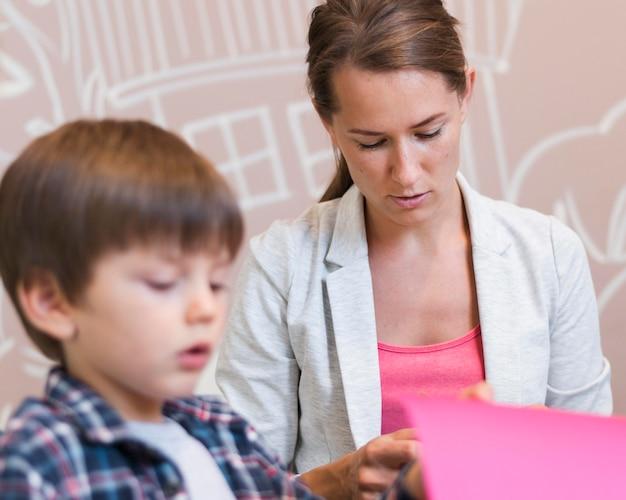 Niewyraźne dziecko i nauczyciel z kolorowym papierem