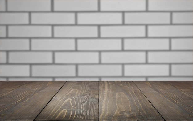 Niewyraźne i abstrakcyjne tło pusty drewniany blat i niewyraźne tło ceglanego muru dla