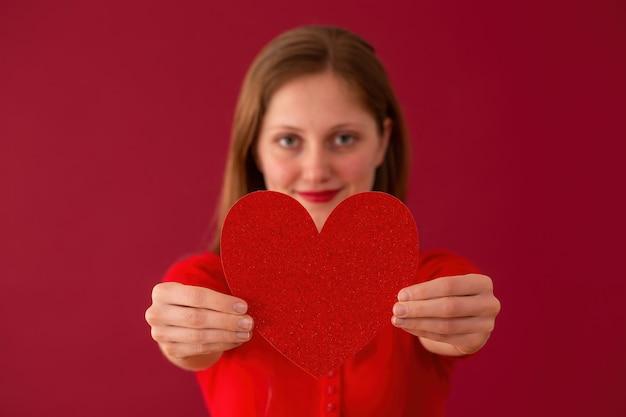 Niewyraźne kobieta pokazuje serce do kamery na czerwonym tle