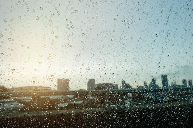 Niewyraźne kropla w oknie samochodu i światło słoneczne nad miastem rano