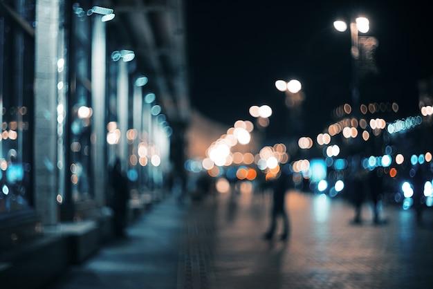 Niewyraźne miasto nocą. bokeh. piękny abstrakcjonistyczny tło z defocused budynkami, samochodami, miast światłami, ludźmi