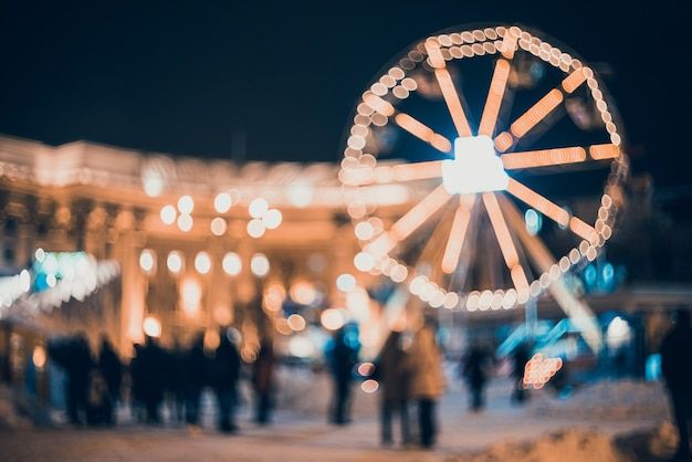 Niewyraźne miasto z lampkami bożonarodzeniowymi w nocy.