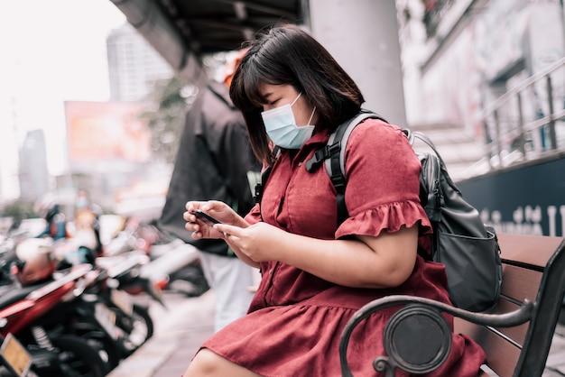 Niewyraźne miękkie obrazy azjatyckiej grubej kobiety noszącej maskę chirurgiczną zapobiegającą powstawaniu kurzu lub wirusa pm 2,5, siedzącej na krześle i korzystającej z telefonów komórkowych w mieście wobec ludzi i koncepcji opieki zdrowotnej.