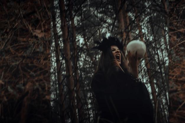 Niewyraźne mistyczne odbicie czarnej wiedźmy z czaszką w dłoniach wykonującej satanistyczny rytuał w ciemnym lesie