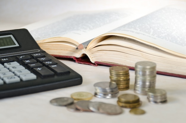 Niewyraźne monety w stosach i kalkulator. pojęcie wysokich kosztów edukacji dla mieszkańców biednych krajów