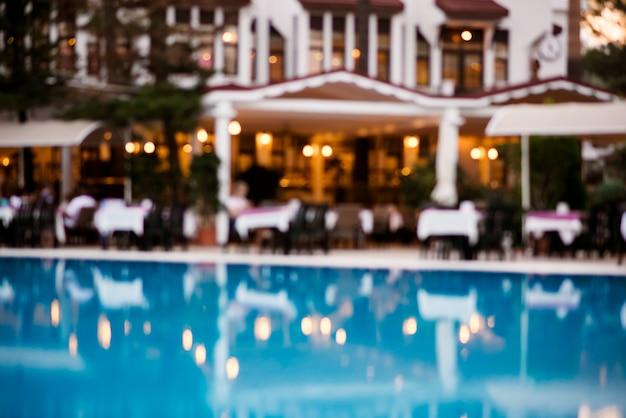Niewyraźne niebieskie baseny i restauracje w tle.