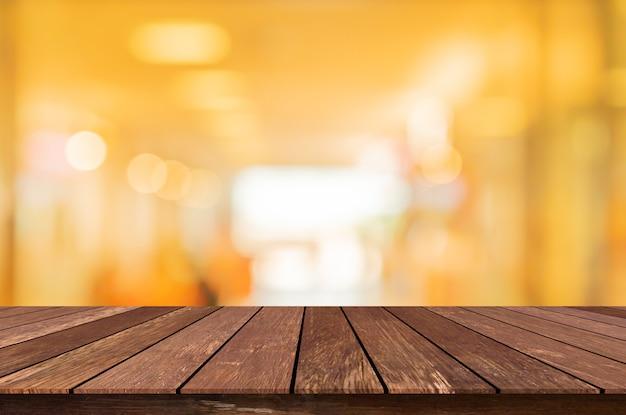 Niewyraźne nowoczesne wnętrze restauracji kawiarnia sklep udekorować żarówki lampy światło na suficie i stolik z drewna