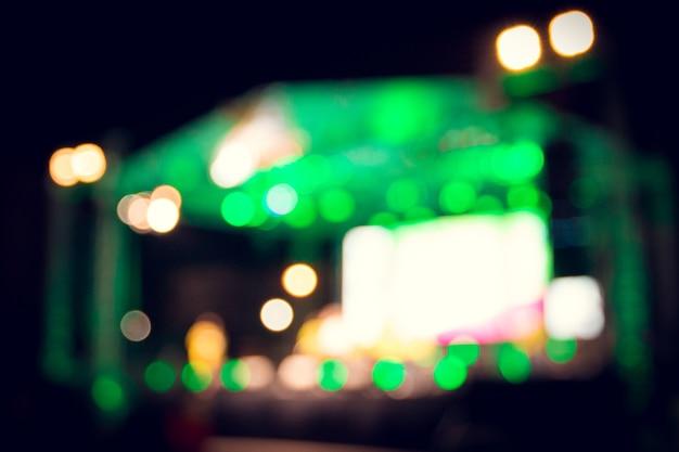 Niewyraźne obrazy sceny koncertowej pełnej świateł bokeh w nocy.