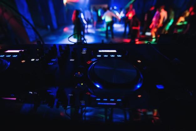 Niewyraźne osoby tańczące na parkiecie w klubie nocnym z mikserem dj z przodu, aby kontrolować muzykę