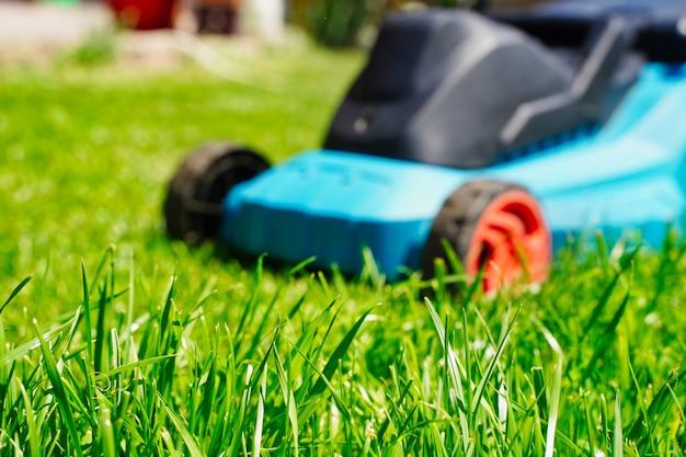 Niewyraźne przycinanie maszyny elektrycznej kosiarki i skupienie się na przycinaniu trawnika na zielonej trawie
