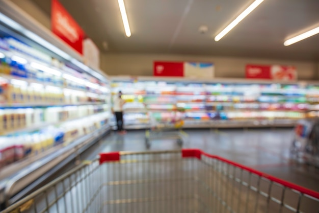 Niewyraźne rozmycie kobiecego napoju mleka żywności zakupu koszyka zakupów umieścić na półce przy drinku w supermarkecie.