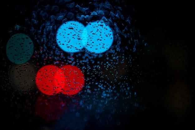 Niewyraźne światła samochodu na mokrych szybach
